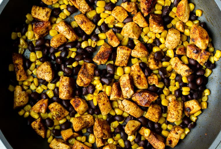 Chunks of chicken, corn, and black beans cooking in a black skillet