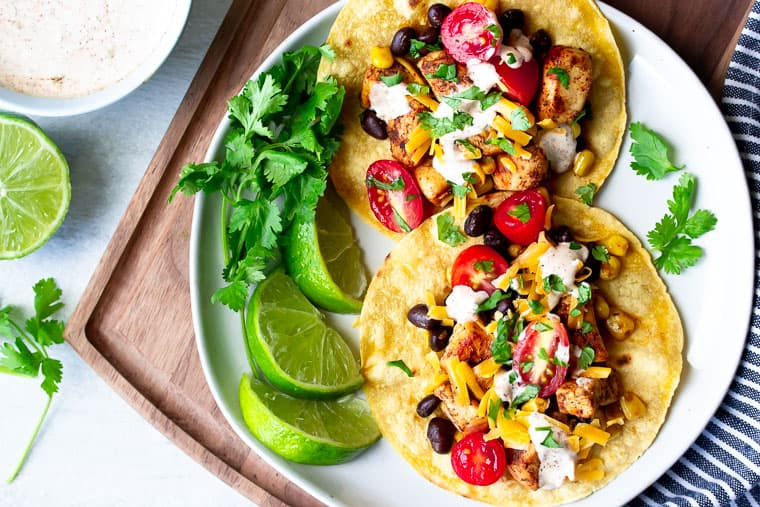Overhead of Chicken Tostadas on a white plate with lime, cilantro, a cutting board, and sauce in a small bowl in the background