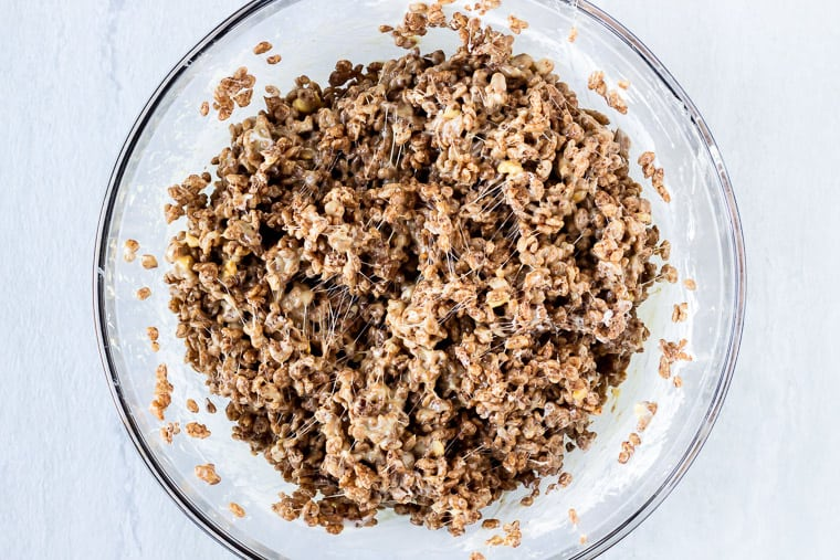 Cocoa Rice Krispies mixture in a glass bowl over a white background