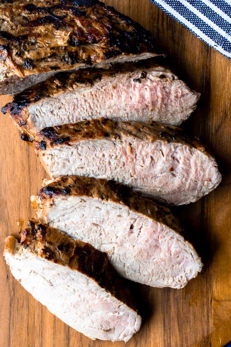 Sliced Cuban Pork Tenderloin on a wood cutting board