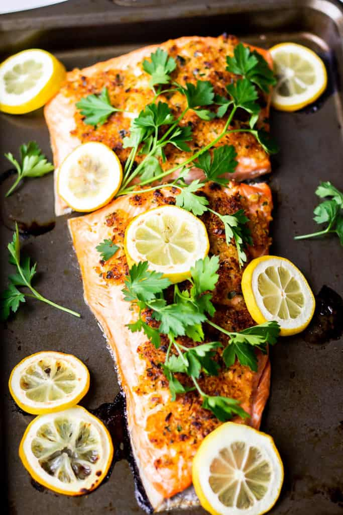 Baked Crispy Lemon Garlic Salmon on a baking sheet topped with fresh parsley and lemon slices with more lemon slices around it
