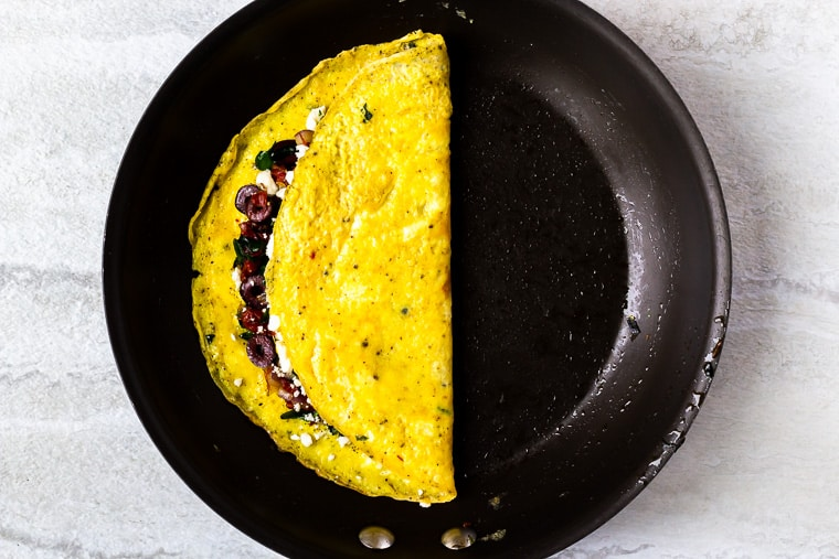 A Greek omelet folded in half in a black skillet over the white background