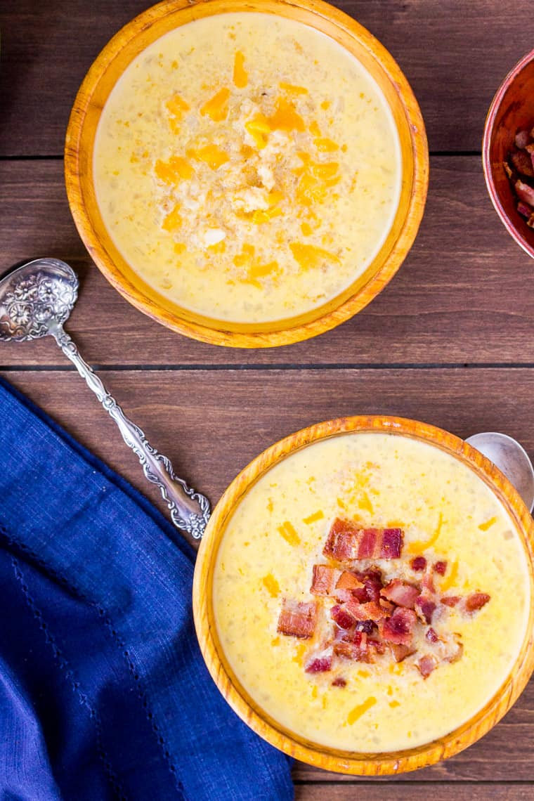 Cheesy Cauliflower Soup in 2 wood bowls with 2 spoons. One bowl of soup has bacon on top. over a wood backdrop