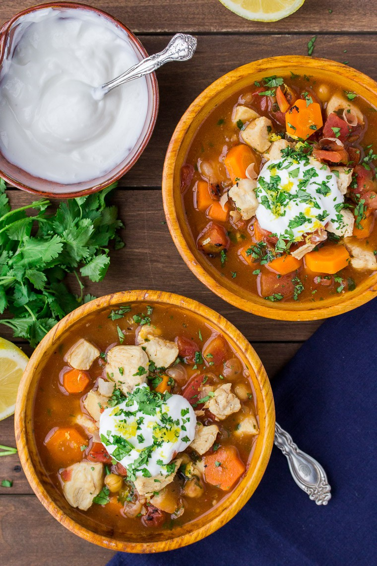 Two Orange Wooden Bowls with Moroccan Chicken Stew, Blue Napkin, and a Bowl of Yogurt