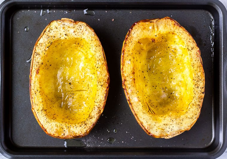 Roasted spaghetti squash halves on a baking sheet