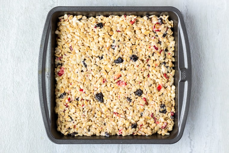 Rice Krispie treats in a square baking pan over a white background