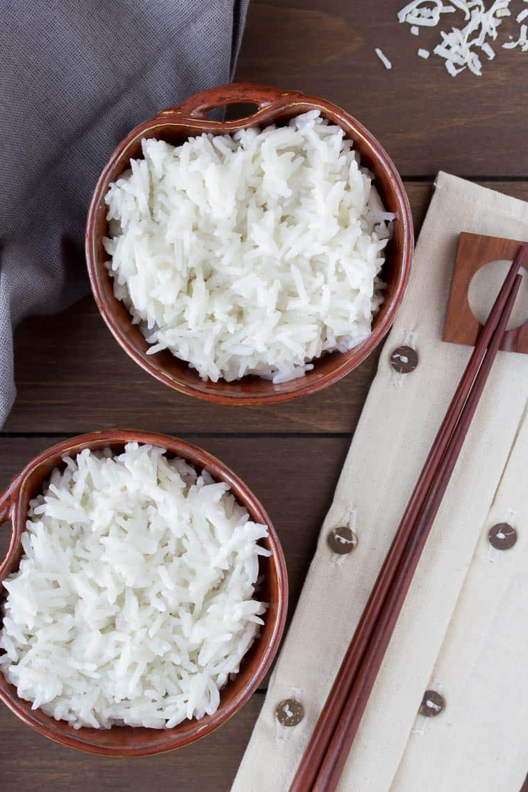 Overhead of 2 brown bowls filled with coconut rice on a wood background with a gray napkin and chopsticks