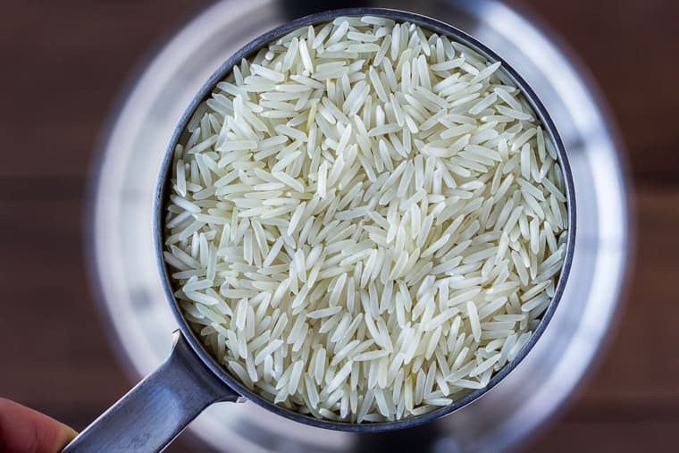 Close up of rice in a measuring cup being held up over a silver pot on a wood background