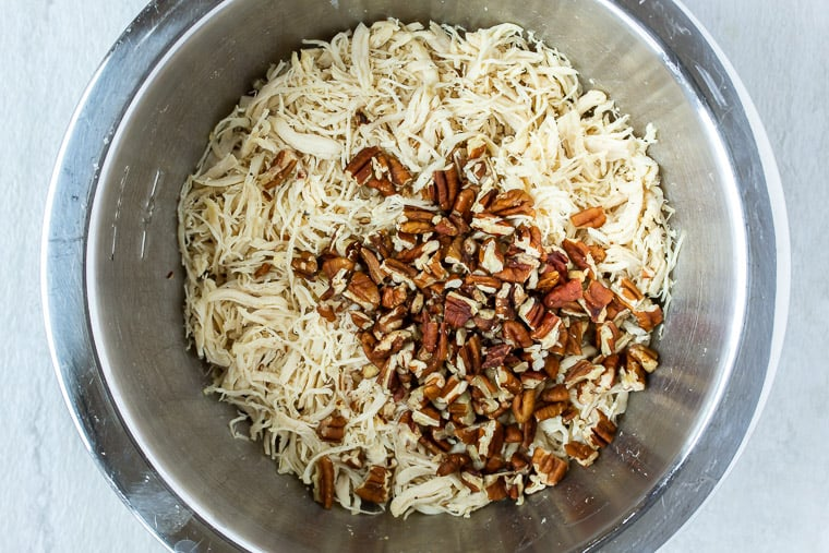 Shredded Chicken and Pecans in a silver mixing bowl