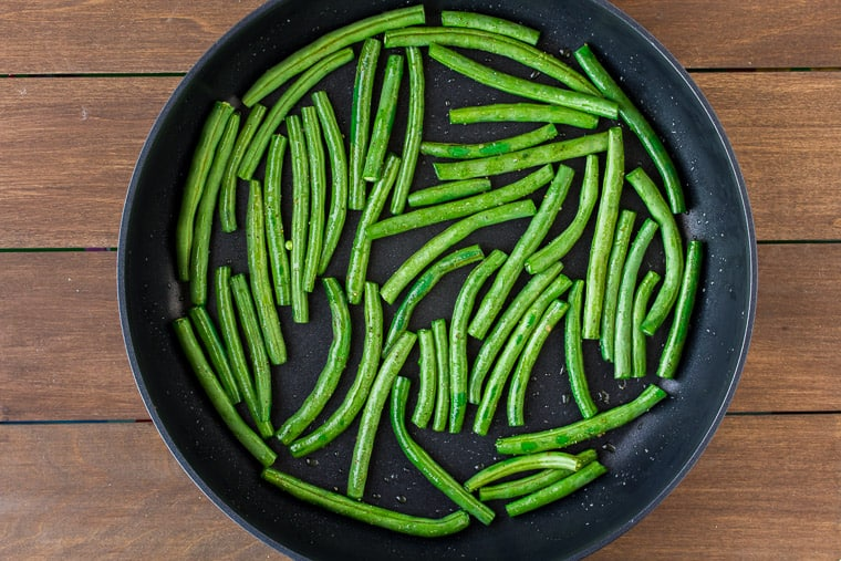 Green beans in a skillet over a wood backdrop
