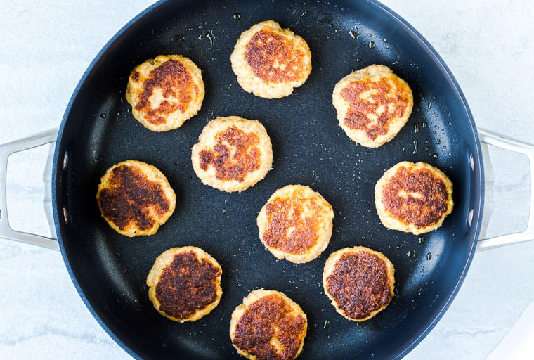 Fried shrimp cakes in a black skillet over a white background