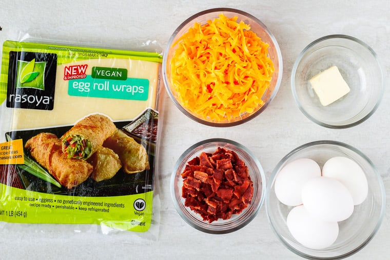Ingredients needed to make breakfast egg rolls laid out on a white background