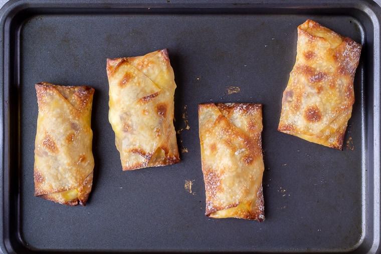 4 Baked egg rolls on a baking sheet