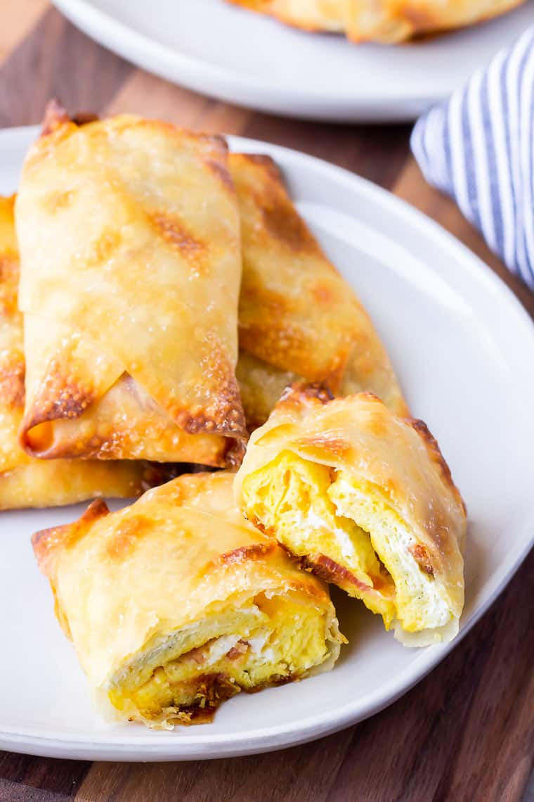 Breakfast egg rolls piled on a white plate with one cut in half over a wood board with a second plate partially showing in the background and a blue and white striped towel