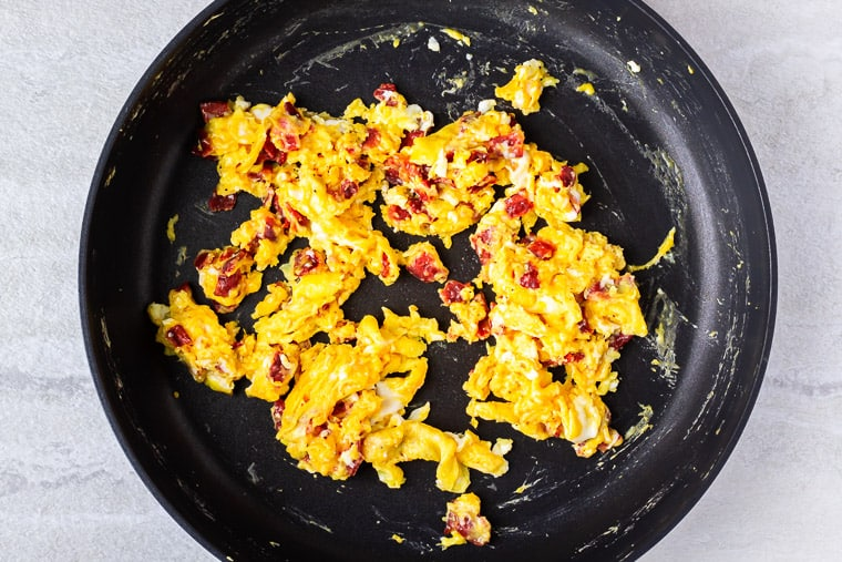 Scrambled eggs with bacon and cheese in a black skillet over a white background