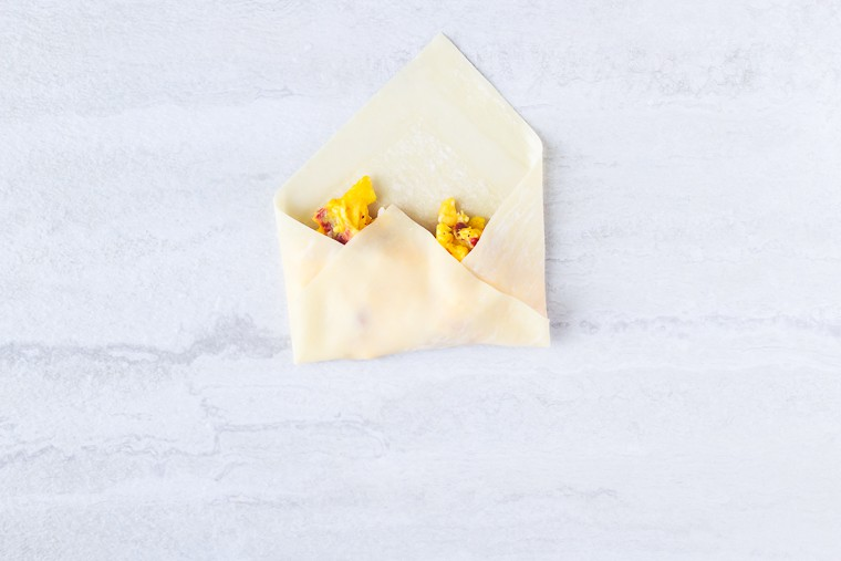 An egg roll wrapper with 3 corners folded in over scrambled eggs on a white background