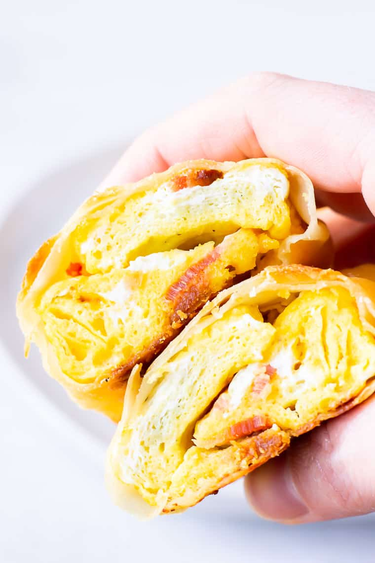 A hand holding 2 halves of a breakfast egg roll over a white background