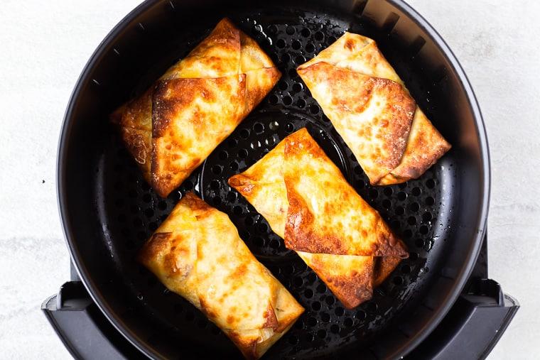 4 air fried egg rolls in an air fryer basket
