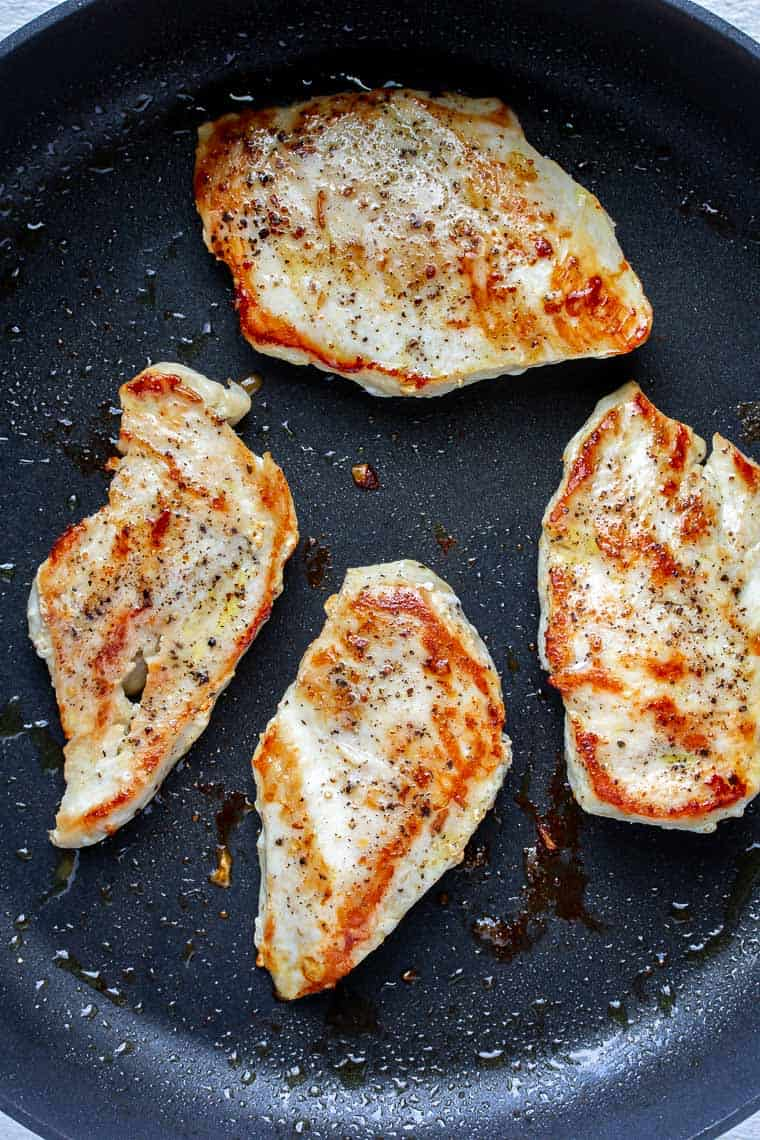 4 Chicken breasts cooking in a black skillet
