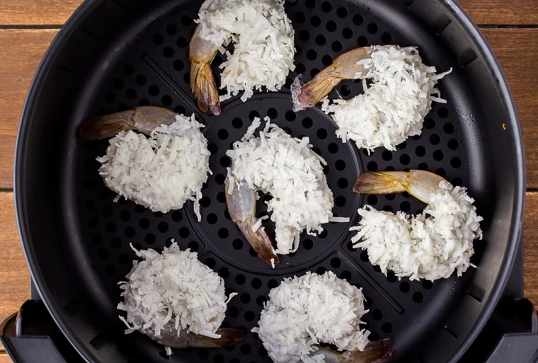 7 uncooked coconut shrimp in a black air fryer basket