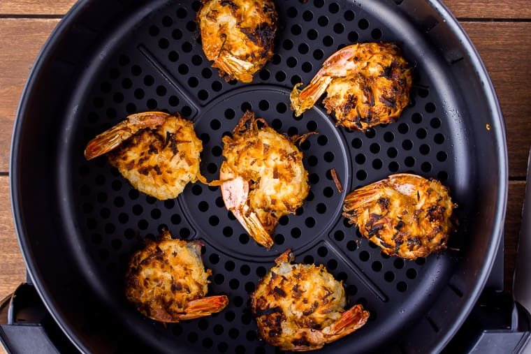Fully air fried coconut shrimp in a black air fryer basket