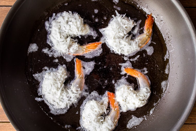 5 large coconut shrimp being fried in a black skillet