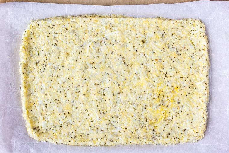 Cauliflower dough formed into a rectangular crust on parchment paper on a pizza stone