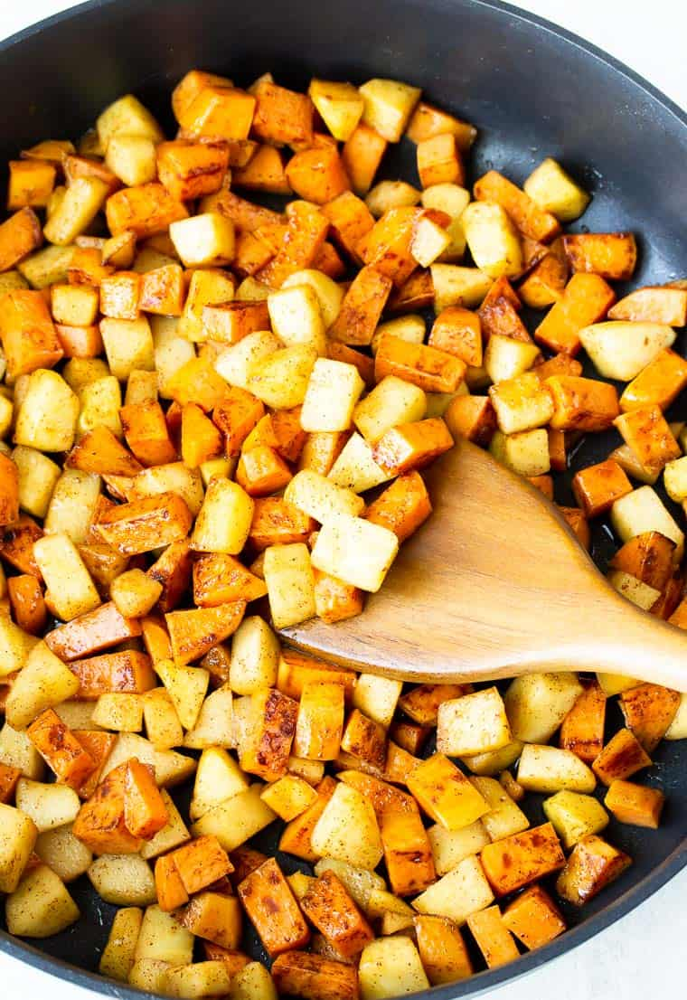 Sweet potatoes and apples in a black skillet with a wood turner
