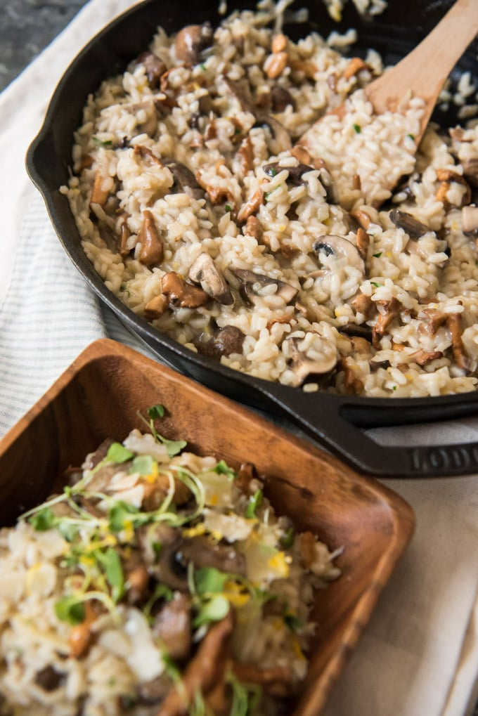 Mushroom Risotto in a cast iron skillet and a wood dish over a white background