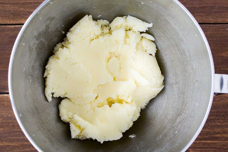 Butter and sugar creamed together until smooth in a silver mixing bowl on a wood background