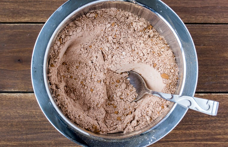 Dry ingredients for chocolate cookies in a silver bowl with a spoon on wood background