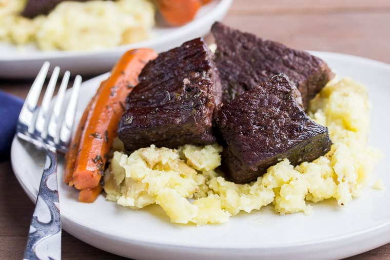 A Plate of Red Wine Braised Short Ribs on Top of Mashed Potatoes with Carrots and a Fork Off to the SIde