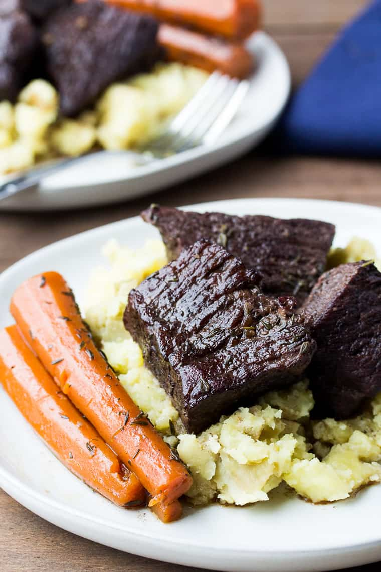 Red Wine Braised Short Ribs on White Plates with Mashed Potatoes and Carrots. All on a Wood Board with a Blue Napkin