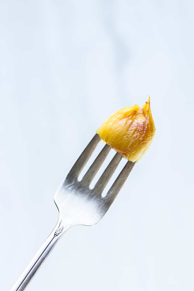 A fork holding a roasted garlic clove over a white background