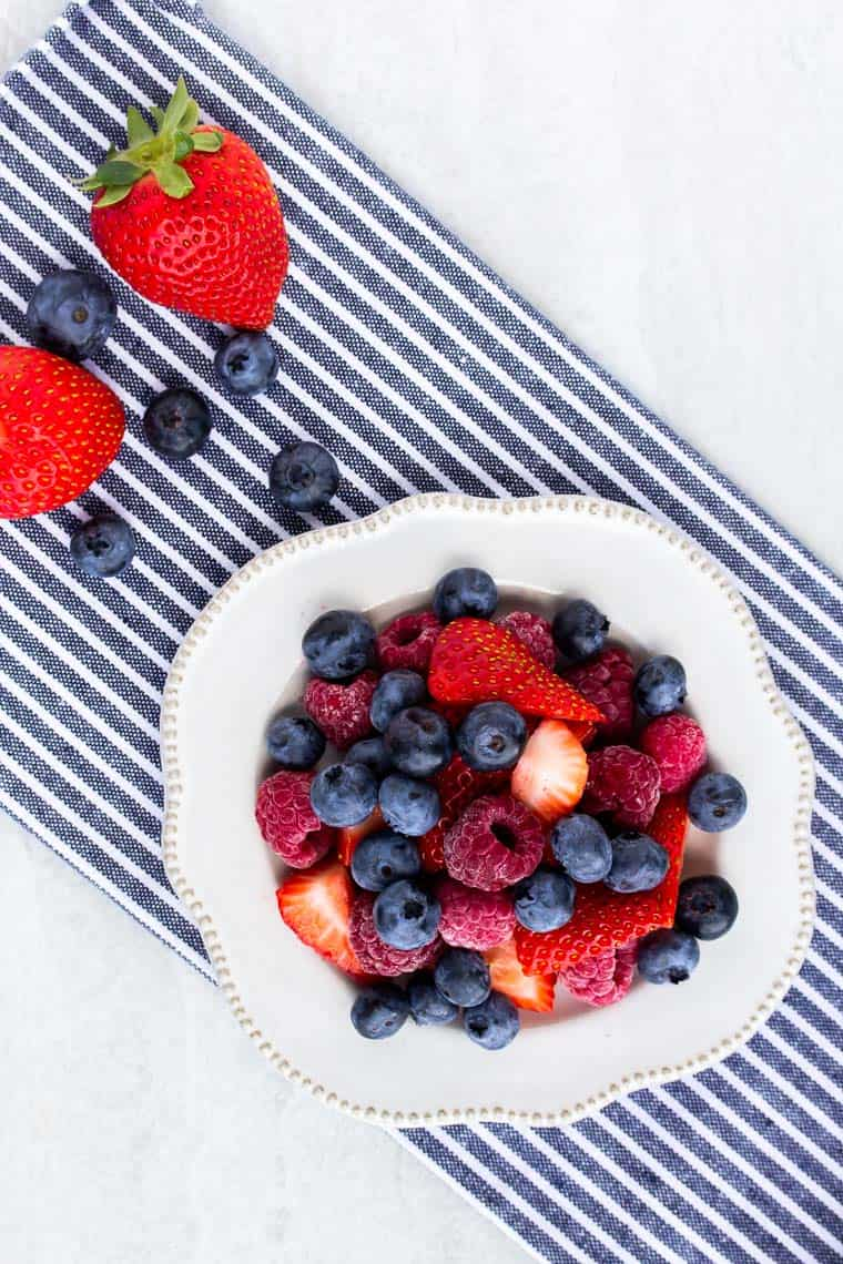 Blueberries, raspberries, and strawberries on a small white plate over a blue and white striped napkin with more strawberries and blueberries in the backgriound