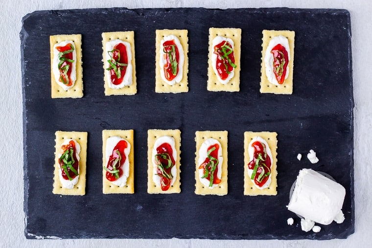10 crackers on a piece of slate that are topped with strawberry jam and basil