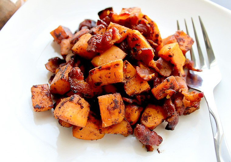 Sweet potato and bacon hash on a white plate with a fork