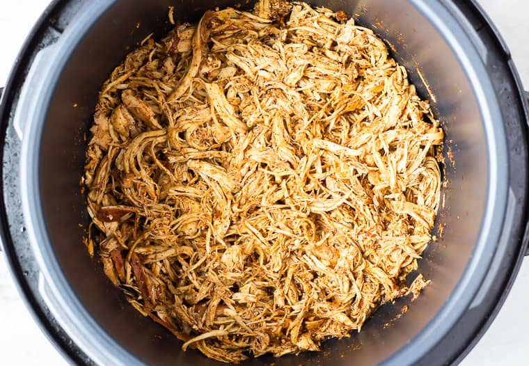 Overhead shredded chicken for tacos in a round slow cooker instant pot