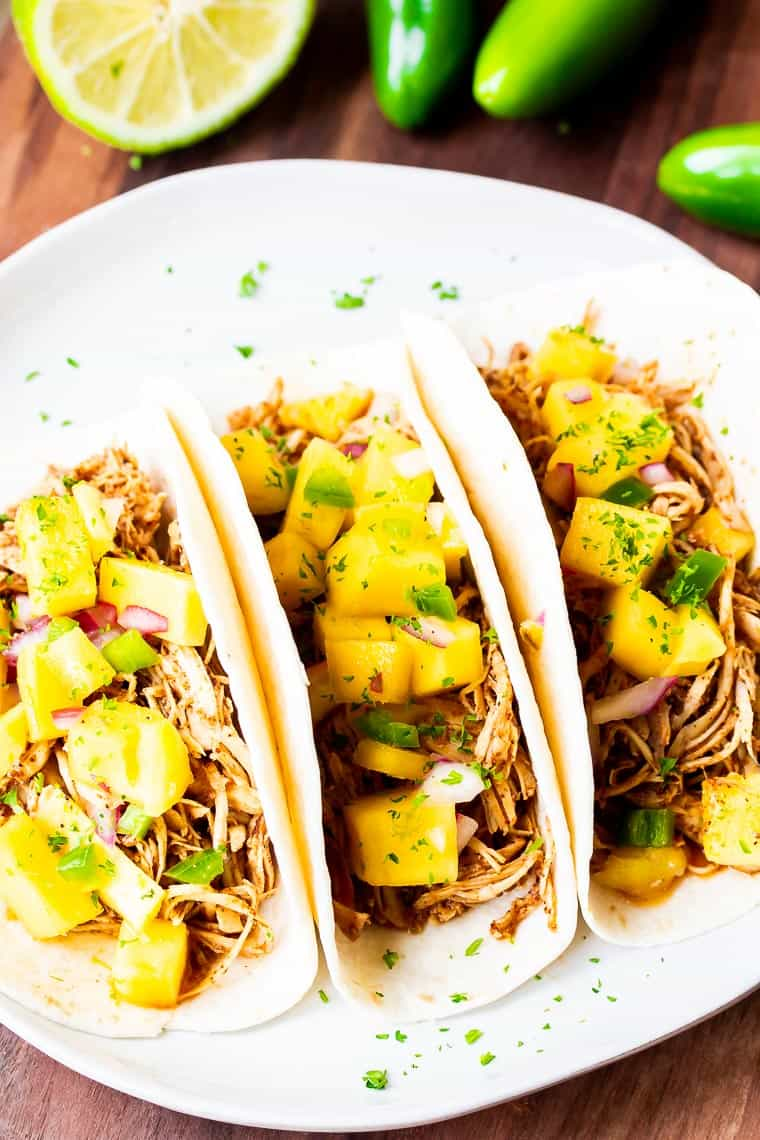 3 Pulled Chicken Tacos in tortillas topped with mango salsa on a white plate over a wood table with a half a lime and 3 jalapeno peppers in the background