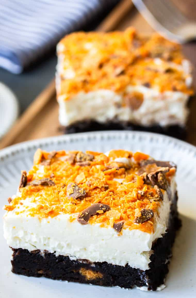 Close up of a Butterfinger Cheesecake Bar on a white plate with a second one in the background with a fork and napkin