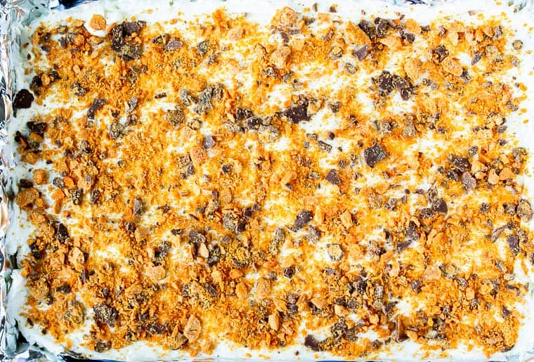 Butterfinger candy on top of cheesecake in a rectangular pan