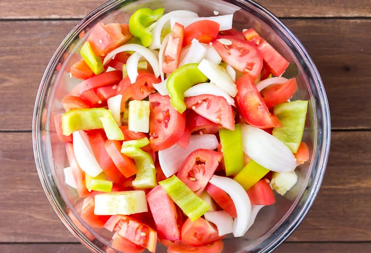 Tomatoes, peppers, onion, and cucumber chunks in a glass bowl over a wood background