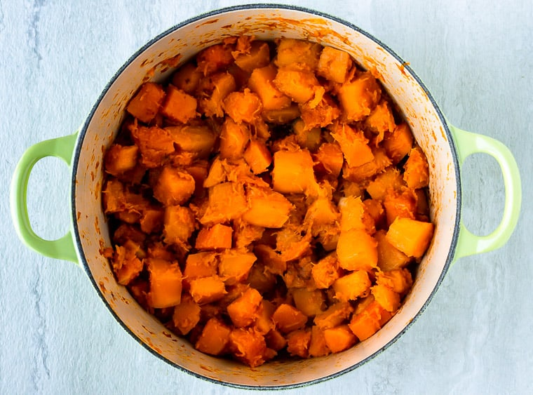 Cooked cubes of butternut squash in a Dutch oven over a white background