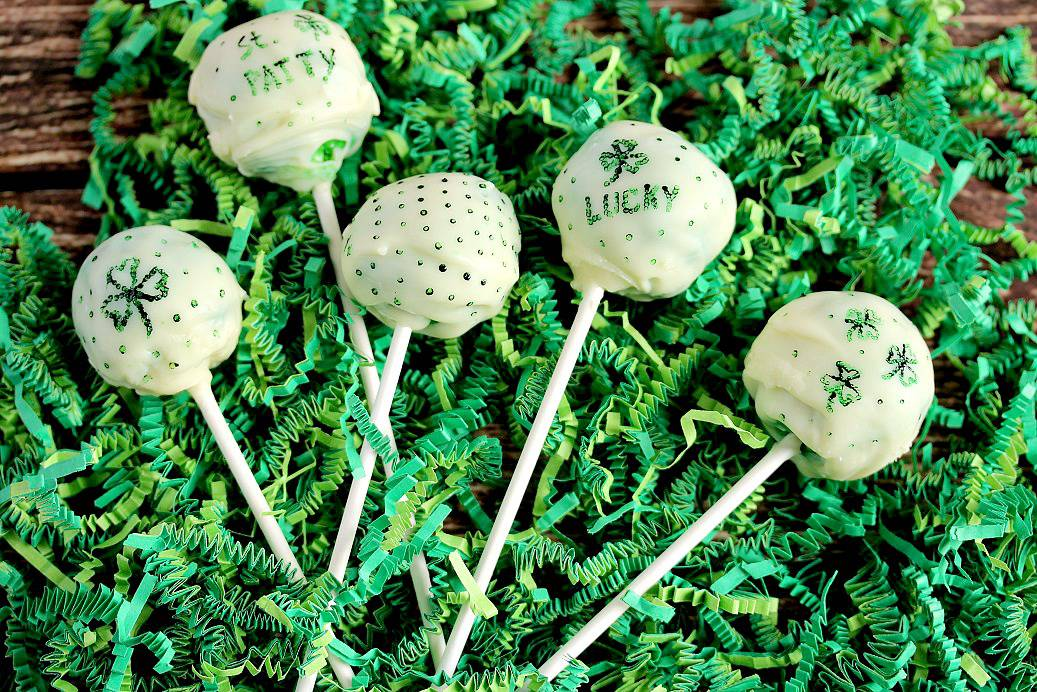 St. Patrick's Day inspired Green Cake Pops laying on green easter grass on a wood board