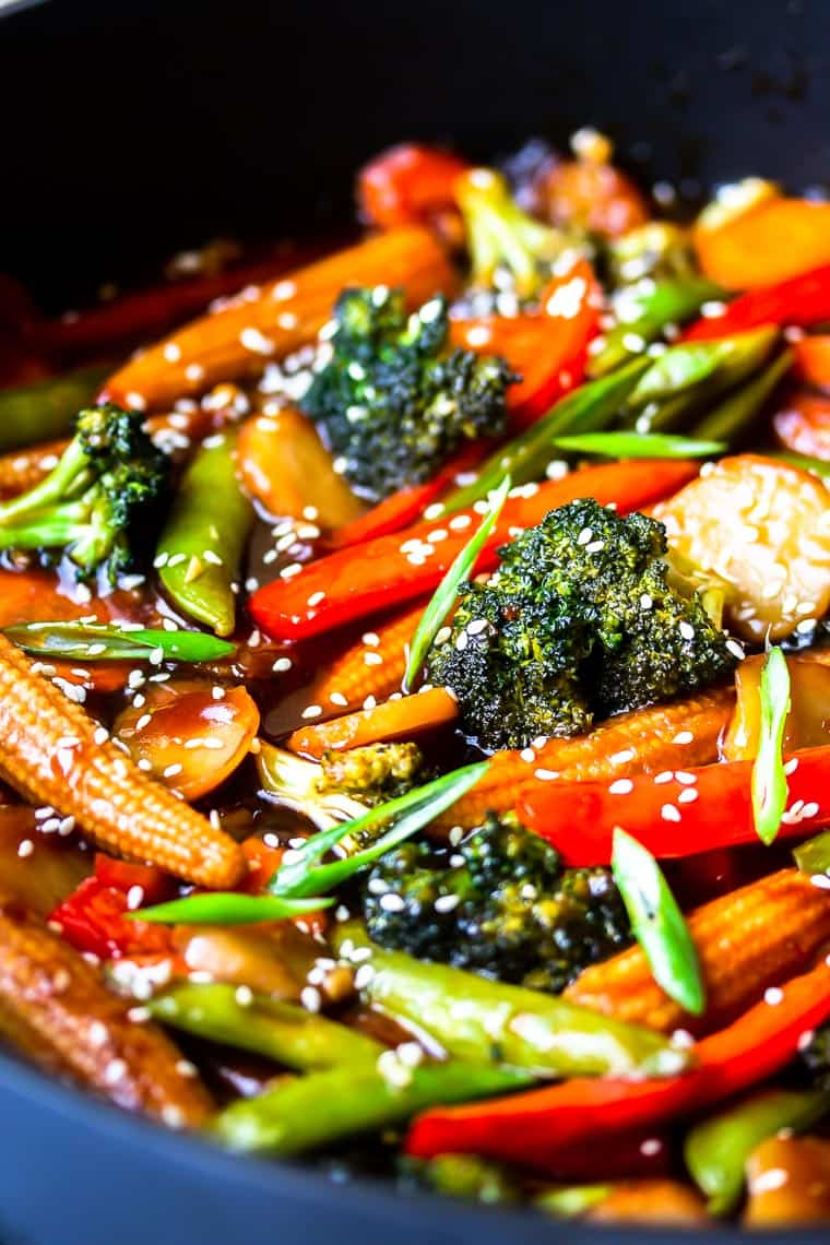 Close up of stir fry vegetables in sauce in a deep, black skillet