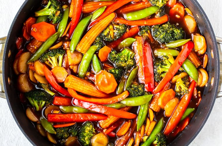 Stir fry sauce and vegetables in a deep, black skillet