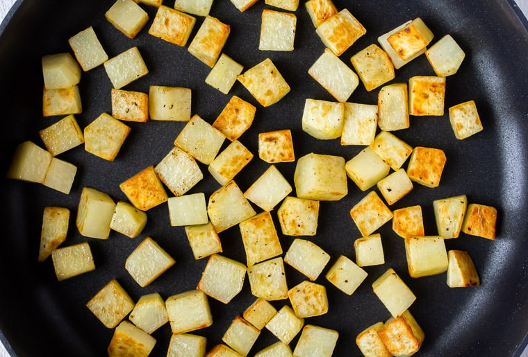 Cooked cubed potatoes in a black skillet