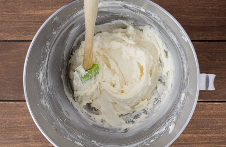 Vanilla Buttercream in a silver bowl with a green and wood spatula