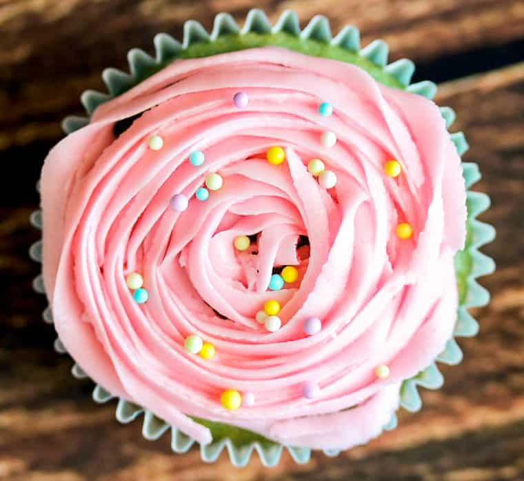 overhead of a cupcake with light pink frosting and pastel round sprinkles over a wood background