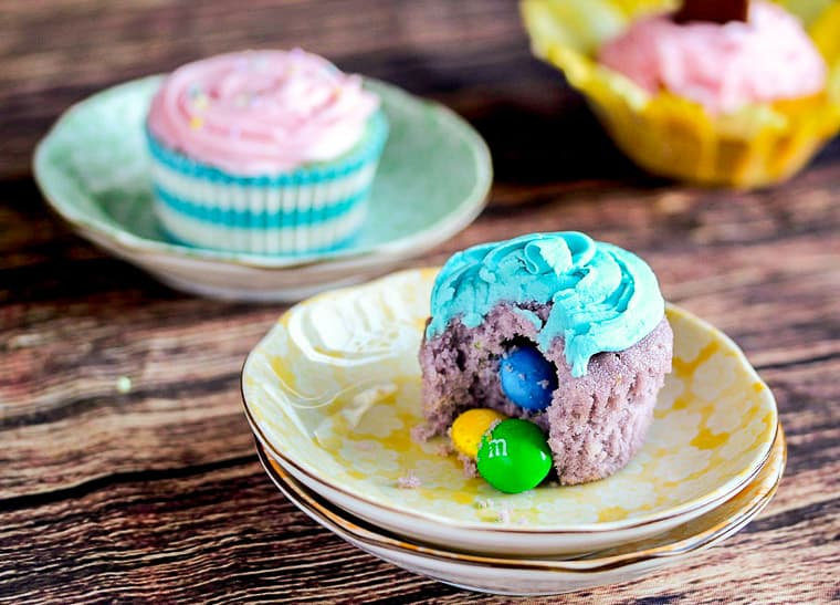 A purple cupcake with blue icing with a bite taken out and candy coming out of the middle. Other cupcakes are in the background on a wood table.